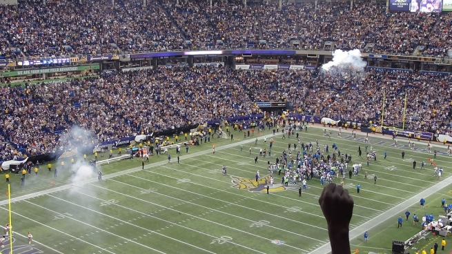 A fan raises a fist in triumph as the Vikings walk out of the Metrodome one last time as winners.