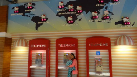 Breeah posing by a set of phones and world time map at the Taiwan airport as we waited for our flight to Guam